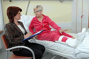 Die Rehaberaterin bespricht den Ablauf des Heilverfahrens mit der Verletzten.